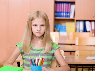 schoolgirl in classroom. looking at camera