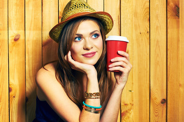 Dreaming Hipster Girl Holding Coffee Cup. Portrait on wooden ba