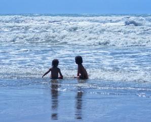Bambine sedute in acqua al mare
