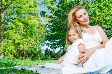 Mother and daughter sitting on cover during picnic