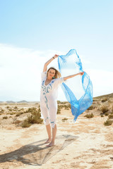 young woman dancing and playing the wind with a transparent veil