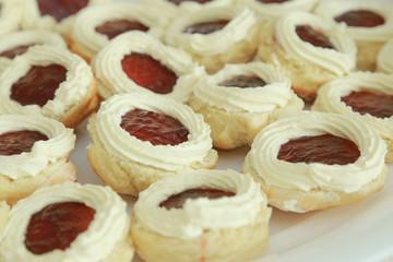 Homemade Jam and cream scones on white plate