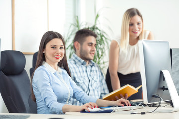 Three young businesspeople working in a office. Focus on beautiful young businesswoman working on a computer and looking at camera while two people talking in the background