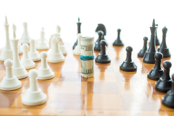 Conceptual photo of twisted money on wooden chessboard