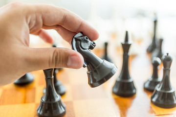 Closeup of male hand holding black horse chess piece