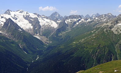 View of the Greater Caucasus Mountain Range from the slope of the mountain Mussa-Achitara in summer sunny day, Dombay, Caucasus, Russia