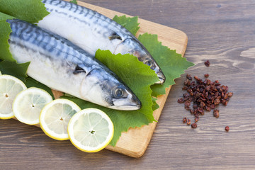 Fresh mackerel in grape leaves with lemon slices