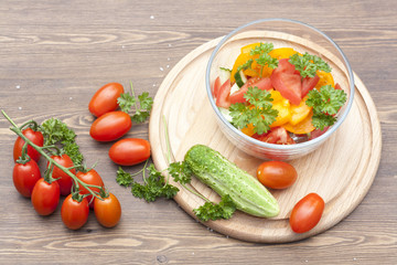 Salad of fresh yellow and pink tomatoes and cucumber with parsley in a glass bowl and vegetables on a wooden table