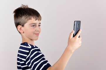 Smiling young boy taking selfie with his smart phone