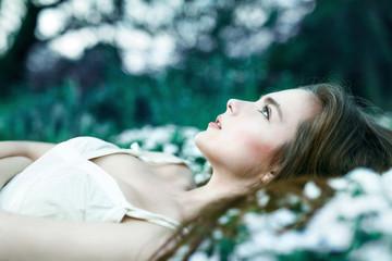 Beautiful sensual girl lying on flower meadow