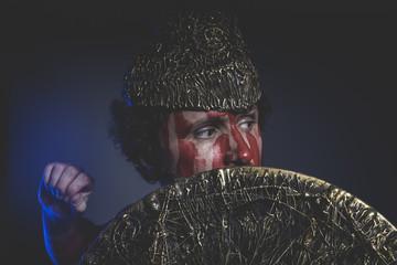 bearded man warrior with metal helmet and shield, wild Viking