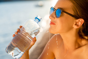 Woman drinking water from transparent bottle on the beach
