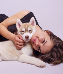 young caucasian female playing with a puppy, girl and siberian husky studio shot on grey background
