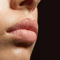 close-up of lips and facial skin in drops of water