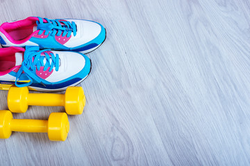 Sneakers and dumbbells fitness on a gray background. Different tools for sport
