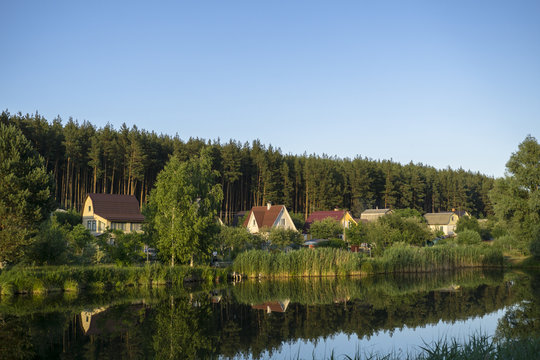 River house with reflections and blue sky near the forest