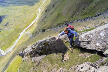 Climber scrambling up Cam Ridge