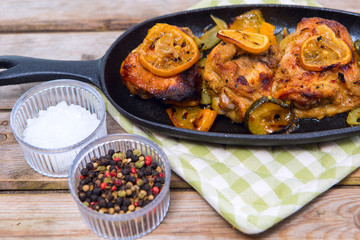 Delicious baked chicken thighs with lemon slices, onion and zucchini