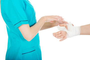 Woman doctor bandaging female hand.