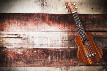 Vintage ukulele on wooden background.