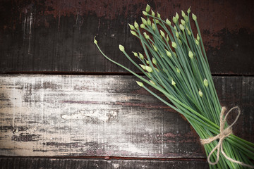 flowering chinese garlic chives on wooden table