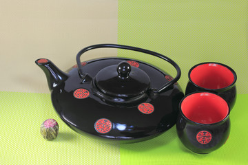 Japanese black kettle with two cups on a napkin