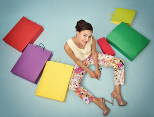 Young cheerful woman with colored paper shopping bags. Shopaholi