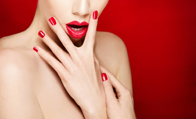 Makeup and cosmetic image. Red lips and manicure.Isolated on red background with copy space.