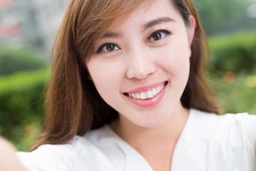 asian beautiful young woman using mobile phone to take selfie ou