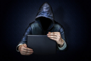 Anonymous hacker with laptop