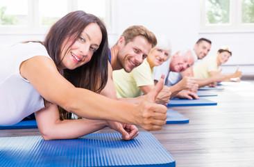 Team mit Daumen hoch beim Training im Fitnessstudio