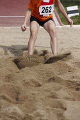 Female long jump competition with woman falling in the sand