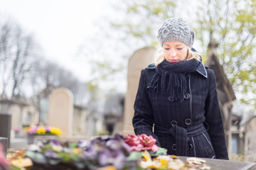 Solitary woman visiting relatives grave.