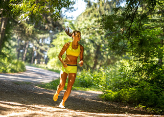 Woman running in wooded forest area, training and exercising on beautiful summer day