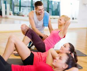 group of smiling women doing sit ups in the gym