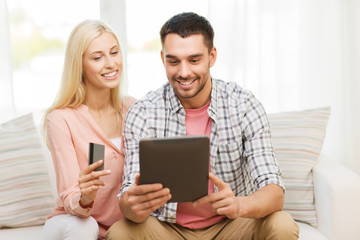 happy couple with tablet pc and credit card
