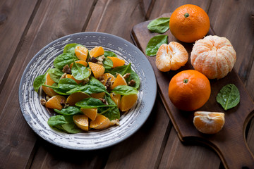 Fresh spinach, tangerines and walnuts salad; dark wooden surface