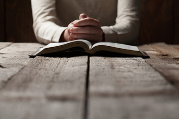 Woman hands praying with a bible in a dark over wooden table Wall mural