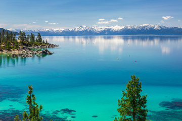 Lake Tahoe calm turquoise waters with view on Sierra Nevada snowy peaks.
