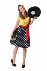 Frau im gepunkteten Kleid hält Langspielplatten