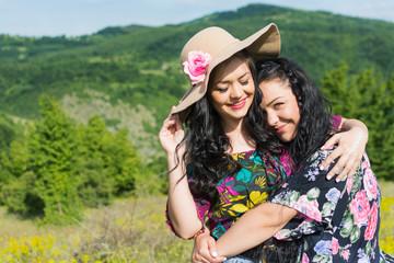 Two beautiful boho sisters hugging