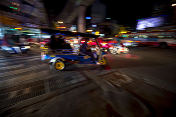 Bangkok Thailand tuk-tuk taxi zooms by in a night blur