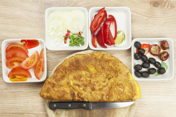 Scrambled egg omelet with vegetables on a wooden table. Preparation of fast food home.