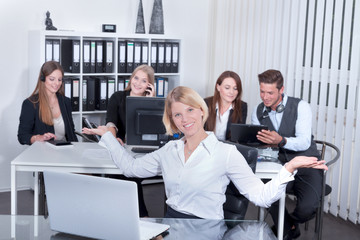 Geschäftsfrau präsentiert zufriedene Mitarbeiter