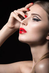 Beautiful girl with unusual black arrows on eyes and red lips and nails. Beauty face. Picture taken in the studio on a black background.