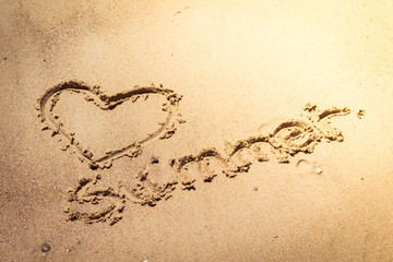 Summer handwritten in the sand of the beach with a lovely heart