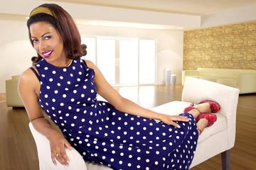 black female sitting on a lounge at home in a blue polka dot dress