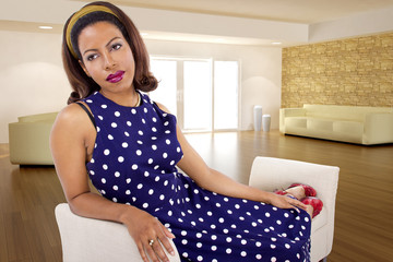 black female sitting on a lounge at home in a blue polka dot dress