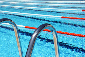 View of lane rope through a pool ladder in an outside Olympic pool.