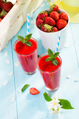 Strawberry smoothie and flower petals on blue background